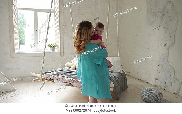 Caring young mom nursing infant child at home
