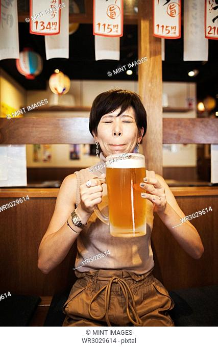 Woman sitting at a table in a restaurant, holding large glass of beer