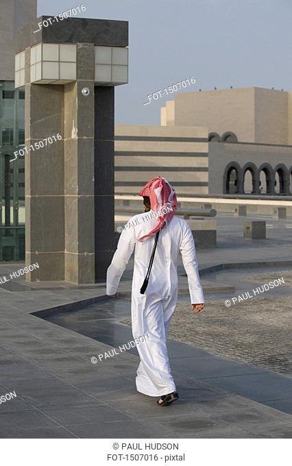 Rear view of Arab man walking on floor against buildings