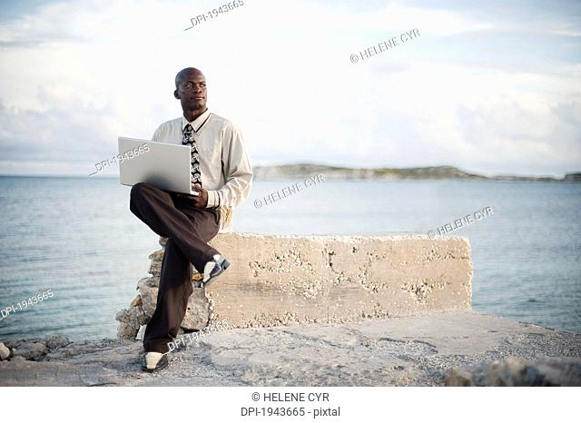 a businessman with a laptop computer sitting on a rock ledge at the edge of the water, south caicos turks and caicos islands
