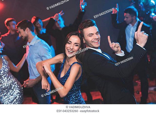 People have fun at the New Year's party. In the foreground, a guy and a girl are dancing. The girl has a blue dress with sparkles, a black suit on the guy