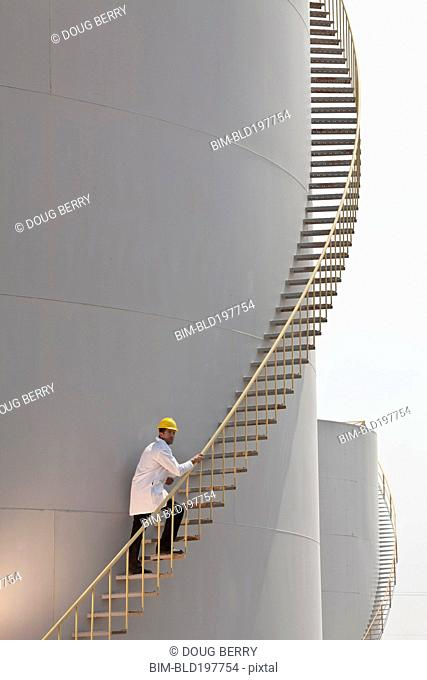 Caucasian worker climbing staircase on storage tank