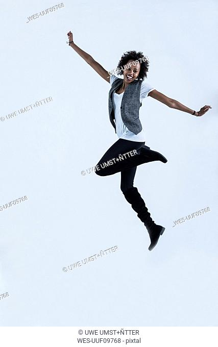 Woman jumping in the air in front of grey background