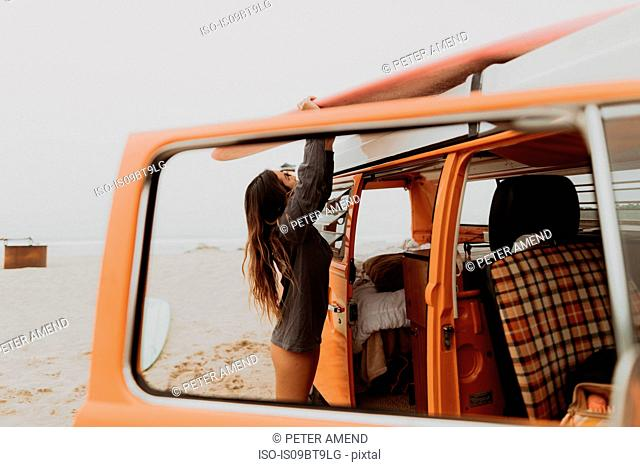 Young female surfer removing surfboard from recreational vehicle roof at beach, Jalama, California, USA