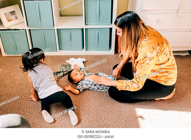 Girl crawling on nursery floor while mother dressing baby brother