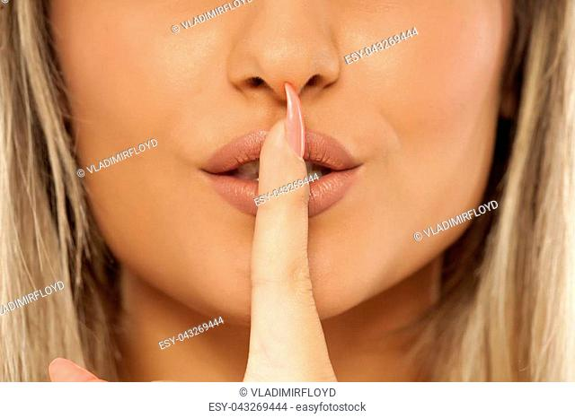 Index finger over her mouth. Silence concept