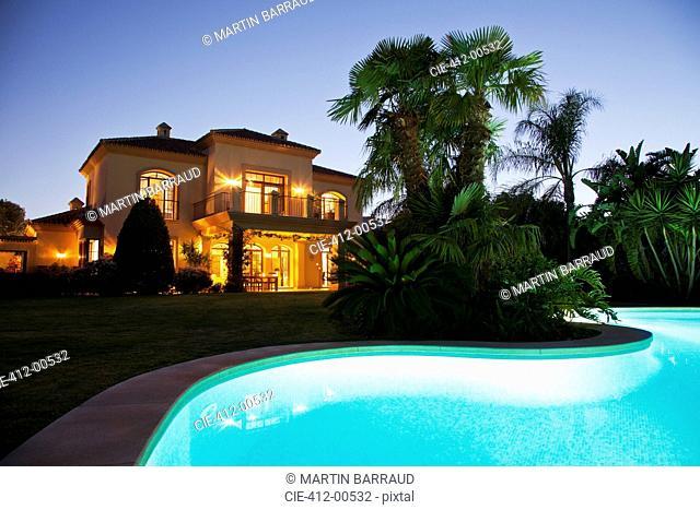 Luxury swimming pool and villa illuminated at night