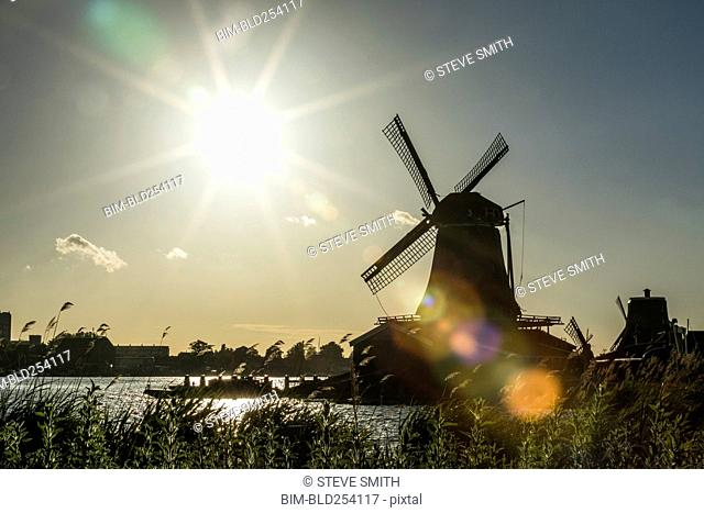 Silhouette of windmill at waterfront