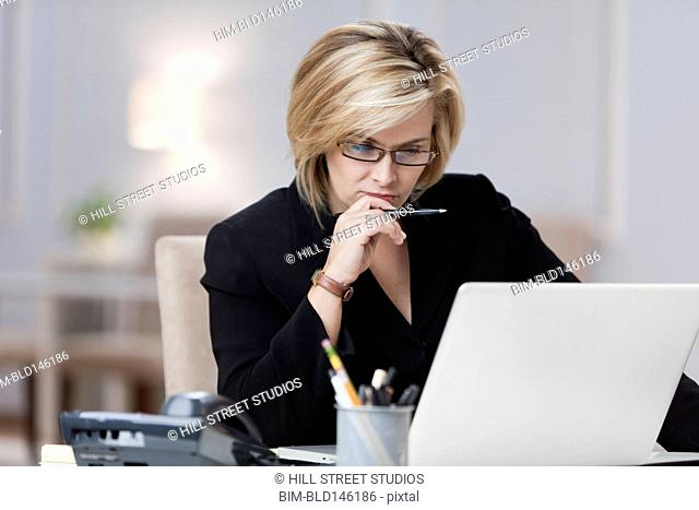 Caucasian businesswoman using laptop in home office
