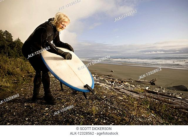 Local surfer from Homer Alaska, 'The Iceman', Don MacNamara, waxing his board, Southeast Alaska; Yakutat, Alaska, United States of America