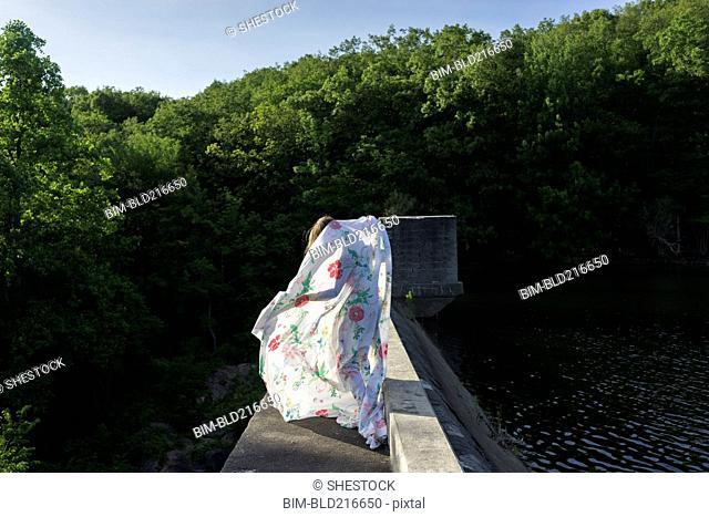 Woman playing with fabric on stone bridge