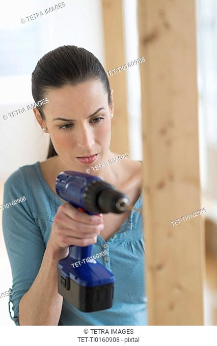 Woman using hand drill