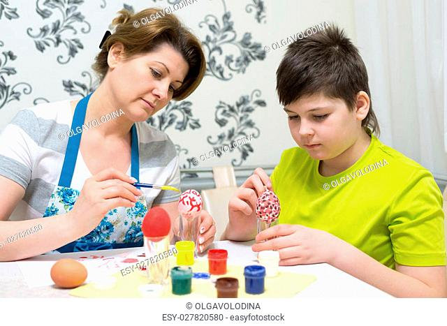 Mom and son paint a Easter eggs