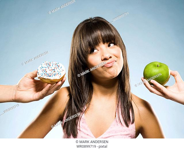 Woman deciding between a donut and green apple