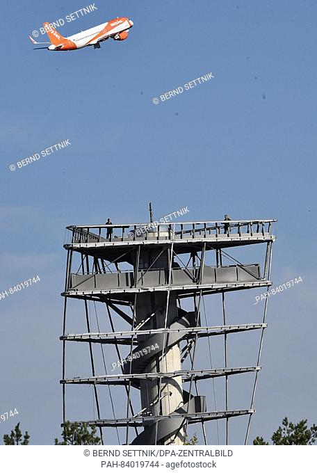 An aeroplane from easyJet takes off ifrom Schoenefeld past the skeleton of the former Infotower of the BER airport in Berlin, Germany, 19 September 2016