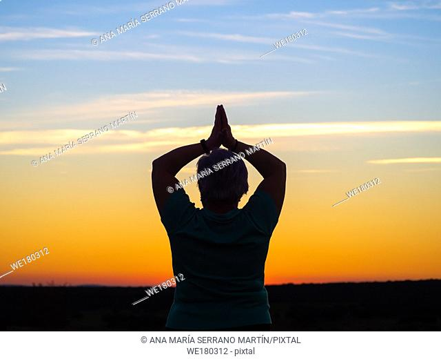 A senior woman practicing yoga at sunset