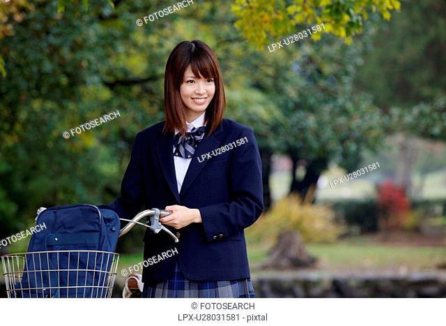 High school girl pushing bicycle
