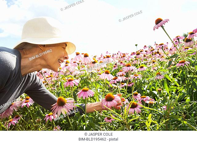 Smiling Caucasian woman looking at flowers