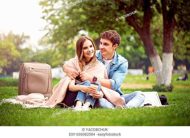 Warm atmosphere. Smiling and cheerful young lovely couple sitting on the grass in the park, arming each other and drinking coffee