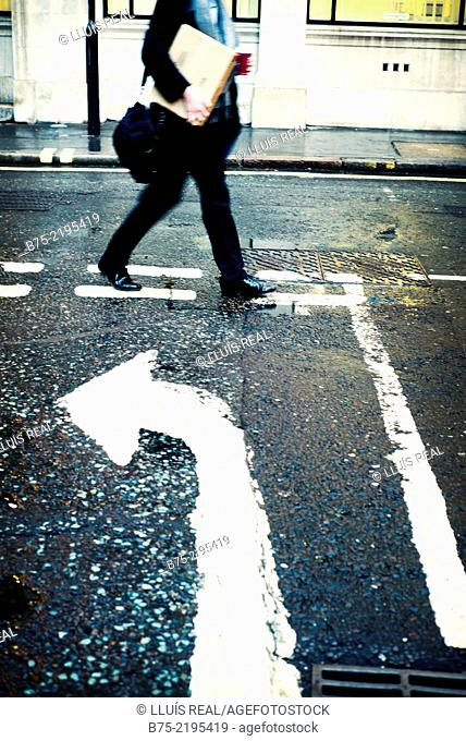 Unrecognizable businessman with a box and a coffee walking down in the street with a turn arrow painted on the asphalt in the city of London, England, UK