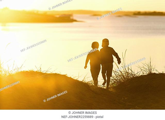 Children walking at sunset