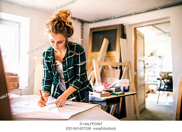 Small business of a young woman. Beautiful young woman worker in workroom. Female carpenter sketching a project