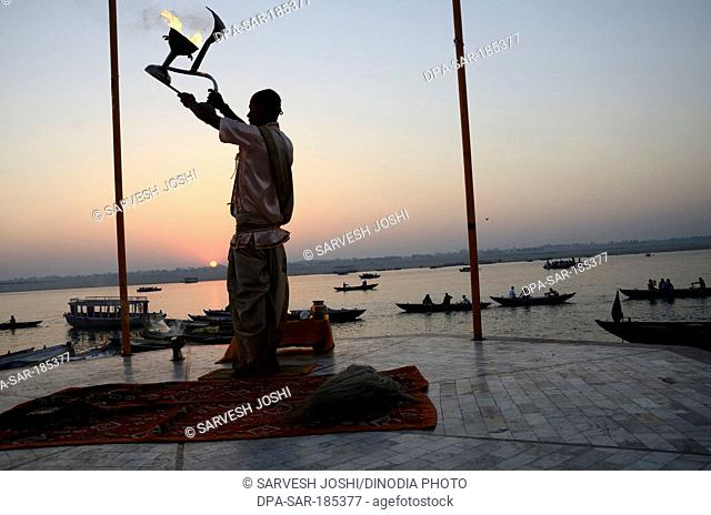 priest performing ceremonial adoration on Ganga river in Varanasi Uttar Pradesh India