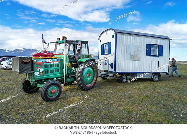 Homemade caravan being pulled by a farm tractor, in the parking lot of the Jokulsarlon Glacial Lagoon, Iceland