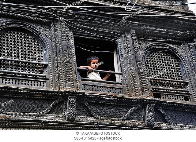 Little boy looking out from the traditional Nepali house precious window at Maru Tole in Hanuman Dhoka Durbar world heritage monument zone