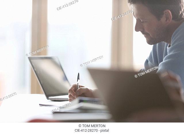 Focused businessman taking notes in meeting