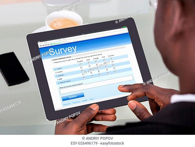 Close-up Of A Businessman Holding Digital Tablet On Desk