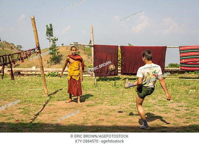 Young men kicking a wicker ball in a small village near Inle Lake, Myanmar