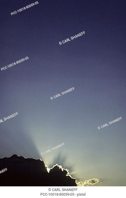 Sun silhouettes a dark cloud with bright rays, blue sky