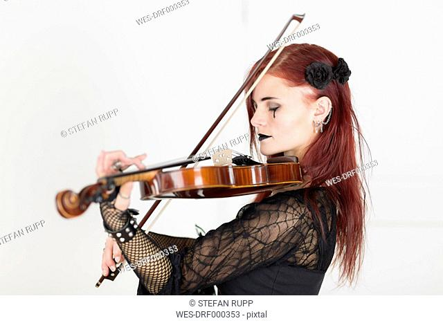 Young woman dressed in Gothic style playing violin with closed eyes
