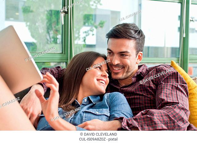 Romantic young couple on sofa with digital tablet