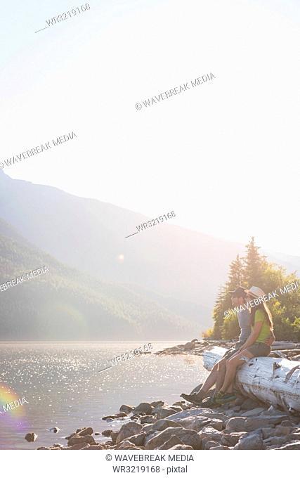 Couple relaxing on wooden log near riverside