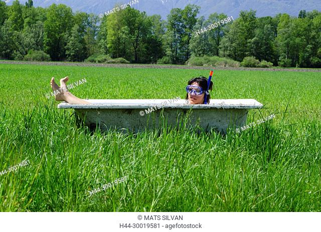 Woman Lying in a Bathtub With Diving Mask on a Green Field in Ticino, Switzerland