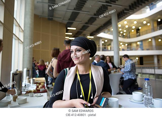 Smiling, confident businesswoman in headscarf at conference