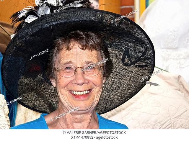This happy and active elderly woman in her seventies is smiling while trying on a big black vintage hat while shopping