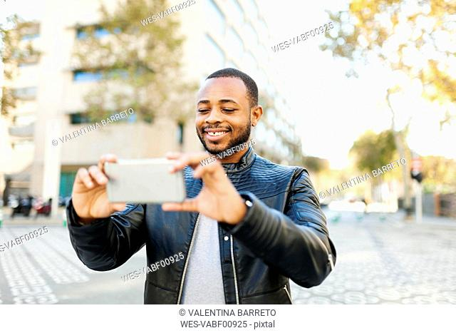 Smiling young man taking selfie with smartphone