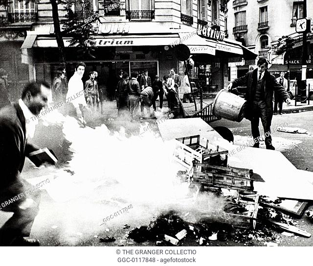 PARIS STUDENT REVOLT, 1968.Students feeding the fire set to a barricade of garbage at Boulevard St. Germain on the Left Bank in Paris, France, 23 May 1968