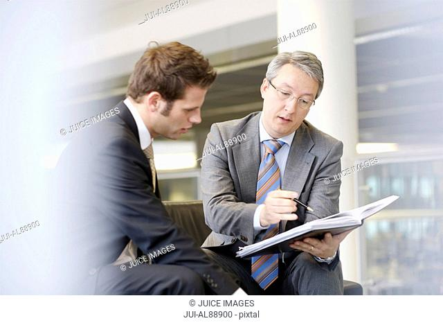 Businessmen discussing paperwork