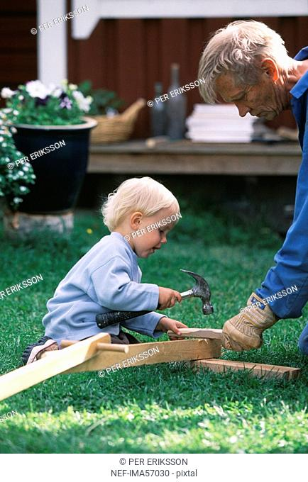 A boy nailing with his grandfather Sweden