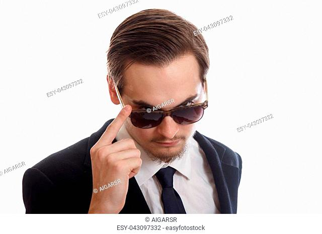 A man in a suit looking over his sunglasses