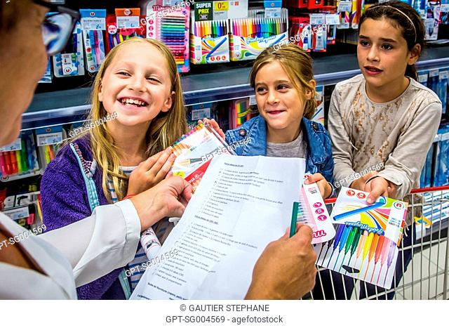 SHOPPING AT THE SUPERMARKET WITH A LIST OF SUPPLIES TO PURCHASE BEFORE SCHOOL STARTS IN SEPTEMBER