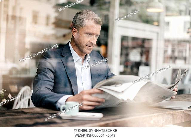 Businessman in cafe reading newspaper