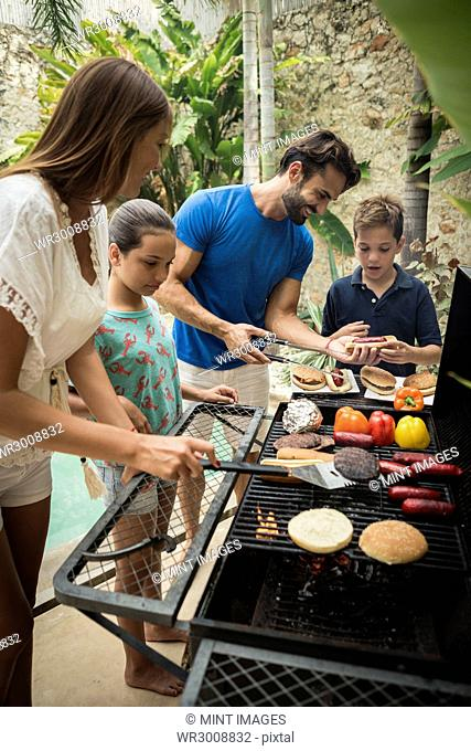 A family standing at a barbecue cooking food