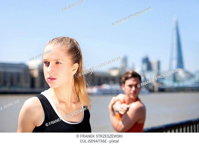 Runners stretching on riverfront, Wapping, London