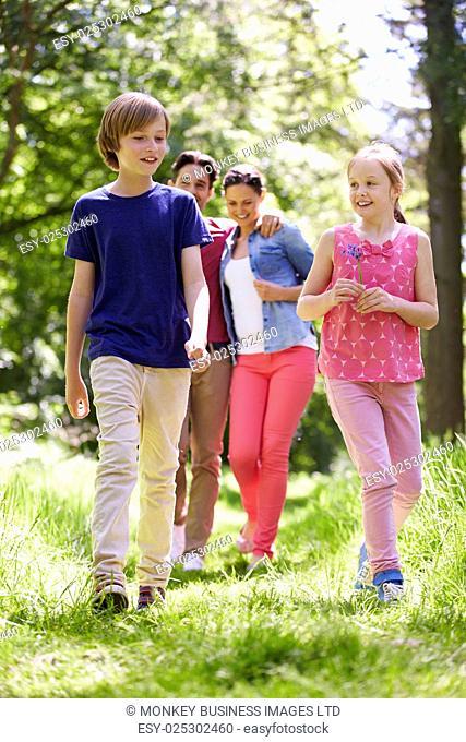 Family Walking Through Summer Countryside