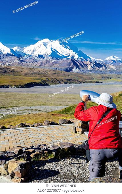 A male visitor views Mt. McKinley through the park provided scope at Eielson Visitor Center in Denali National Park, Interior Alaska, Summer, USA